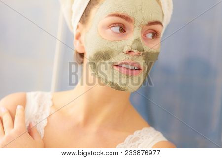 Skin Care. Woman In Bathroom With Green Clay Mud Mask On Face. Girl Taking Care Of Oily Complexion.