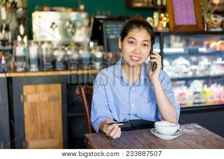 Happy Asian Customer Asking Information About Credit Card While Calling Contact Center. Cheerful Suc
