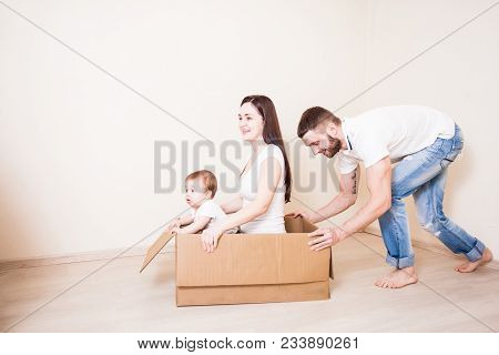 The Young Father Pushes A Box With A Mother And A Baby