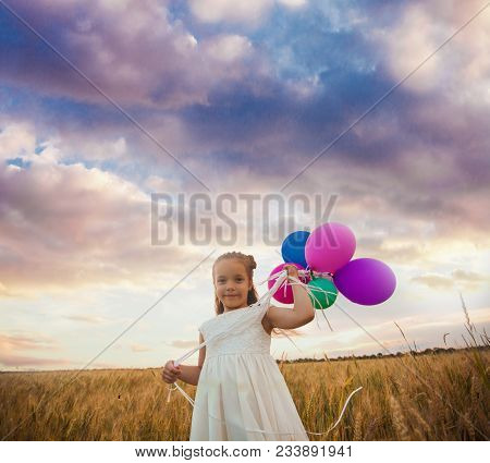 Seven Years Old Girl Holds Balloons In A Hand, Standing Outdoors In The Field. Freedom And Inspirati