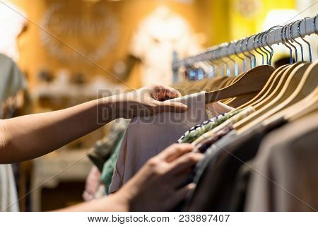 Close Up Of Woman Hand Choosing Thrift Young And Discount T-shirt Clothes In Store, Searching Or Buy
