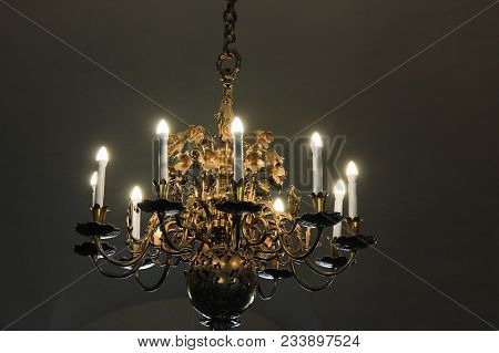 Antique Vintage Chandelier With Lit Candles Isolated On Dark Room Background. Luxury Retro Furniture