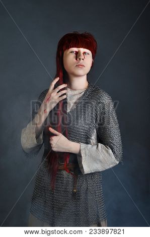 Medieval Girl In Chain Mail With Red Hair Stands On A Gray Background With Blood On Her Hands. Studi