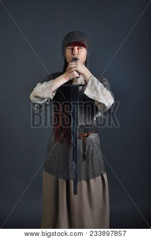 Medieval Girl In Chain Mail With A Sword With Red Hair Stands On A Gray Background With Blood On Her