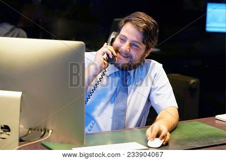 Man Working At Desk In Busy Creative Office. Office Worker Man At The Computer.
