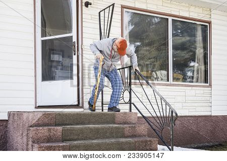 Horizontal Image Of A Caucasian Elderly Man Exiting His Home Down The Cement Steps With A Walking Ca