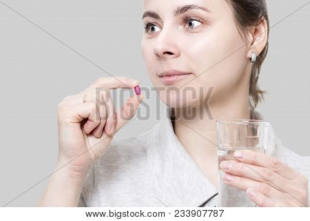 Young Woman Is Holding Red Vitamin Tablet And Glass Of Water. Concept Of Health. The Girl Takes Pill