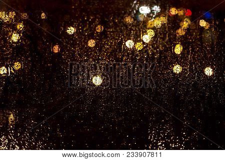 Bright Glowing Bokeh On Wet Glass Against Background Of The Night City Lit By Lights And Lanterns. D
