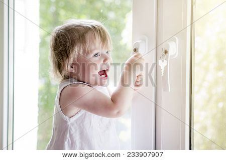 Small Child Near Window. Lock On Handle Of Window. Child's Safety At Window. Do Not Fall Out Of Wind