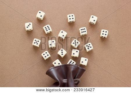 Set Of White Gaming Dice Rolled Out Of Leather Bag On Brown Background. Concept With Copy Space For