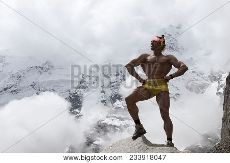 Beautiful Athletic Naked Man Stands On A Rock And Joyfully Stares Into The Distance. The Muscles Are