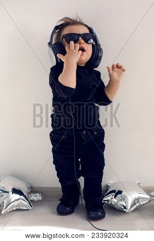 One-year-old Baby In Black Clothes Listening To Rock Music In Big Headphones