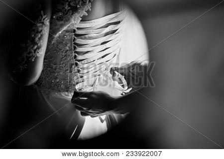 The Bride's Maid Strips Beautiful Ribbons On The Bride's Corset. Black And White Photo