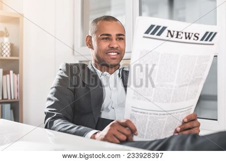 Portrait Of Young African Guy Reading Newspaper. Man In Respectable Suit Sitting Near Table And Smil