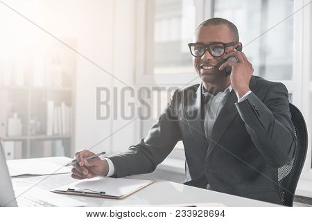 Portrait Of Young African Businessman Sitting At Office And Communicating On Mobile. He With Happy S