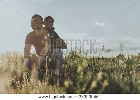 Content Adult Man Squatting On Sunlit Grass, Little Schoolboy Beside Covering His Eyes With Hands. C