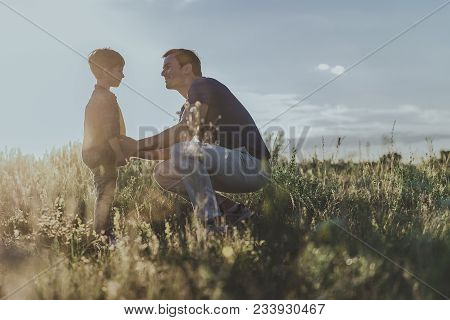 Joyful Male Squatting Down In Front Of Small Boy Standing On Grassland. Copy Space In Right Side