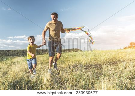 Happy Male With Kite And Boy Running On Sunlit Meadow And Holding Hands. Full Length
