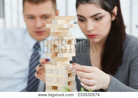 Businessman And Businesswoman Plays In Strategy Of Jenga Hand Rearranging Wooden Blocks Involved Dur
