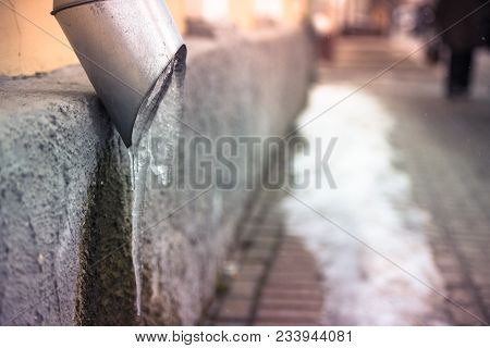 Drain Pipe On The Wall Of The House With Frozen Water Along The City Sidewalk
