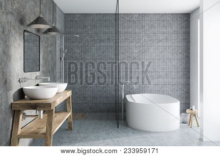 Gray Tile Bathroom Interior With A Concrete Floor, A White Bathtub, A Double Sink Standing On A Wood