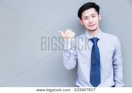 Portrait Handsome Asia Businessman: Attractive Young Businessman Is Pointing His Thumb To Copy Space