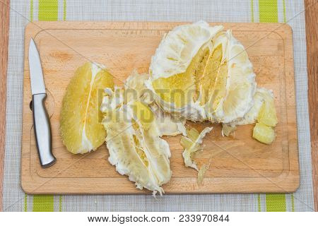 Cleansed Pomelo And Knife Lying On A Wooden Board