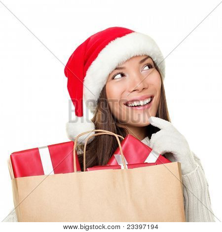 Christmas shopping woman thinking wearing santa hat and holding gifts in shopping bag. Thinking mixed race Chinese Asian / Caucasian female looking sideways smiling happy isolated on white background.