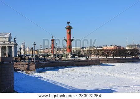 Saint Petersburg, Russia, Winter Cityscape View With Rostral Columns Across Frozen Neva River From P
