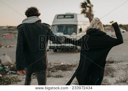 Alternative Couple Holding Hands And Running Towards Their Van With Excitement.