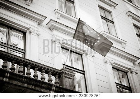 European Union Flag, Old City Building On The Background. Blue European Union Flag With Yellow Stars