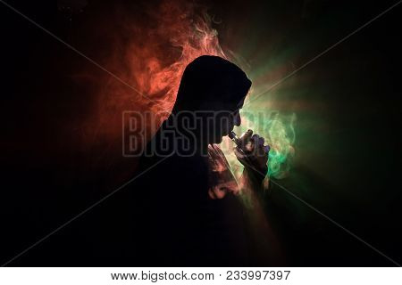 Vaping Man Holding A Mod. A Cloud Of Vapor. Black Background. Vaping An Electronic Cigarette With A