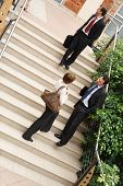 A view of a several people belonging to a business team standing on the steps of an office building having informal conversation as they leave following an important meeting. poster