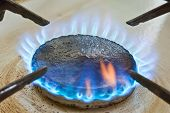 Blue flames from gas stove burner. Shot of blue flames from a kitchen gas range. poster