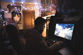 Gamer with Beard plays games on a home computer. A young man sits at home in his room and plays games on a computer. Game of the race on the computer. poster