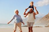Grandparents Carrying Grandson On Shoulders On Walk Along Beach poster
