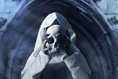 A woman in white hooded cloak holding a human skull in front of her face on temple arch background. poster