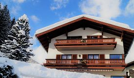 Traditional Alpine Ski Chalet. A Typical Villa In The Austrian Alps After A Winter Snowfall.