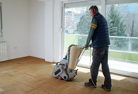 Sanding Hardwood Floor With The Grinding Machine. Repair In The Apartment. Carpenter Doing Parquet W