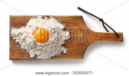 Heap Of Flour And Egg Yolk On Wooden Cutting Board, Top View