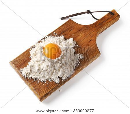 Heap Of Flour And Egg Yolk On Wooden Cutting Board Isolated On White Background
