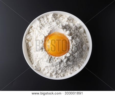 Bowl Of Flour And Egg Yolk On Black Background, Top View