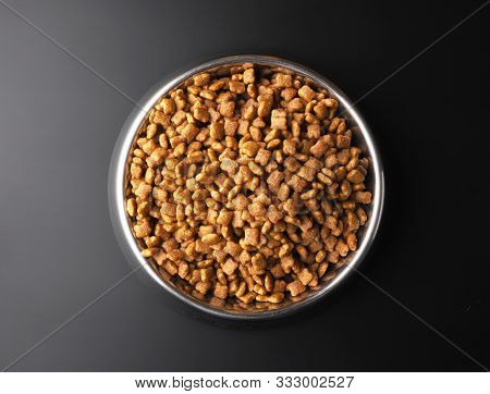 Dry Pet Food In A Metal Bowl On Black Background, Top View