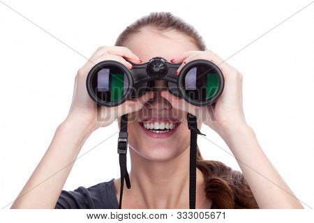 Young smiling woman looking through binoculars isolated on white background