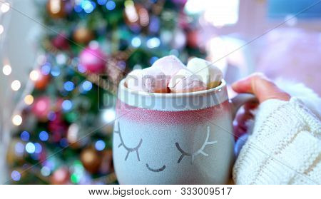 Woman Holding Hot Chocolate In Front Of Christmas Tree.