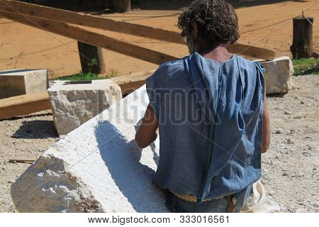 Senior Sculptor Working Outdoor On His Marble Sculpture In His Workshop With Hammer And Chisel Guede