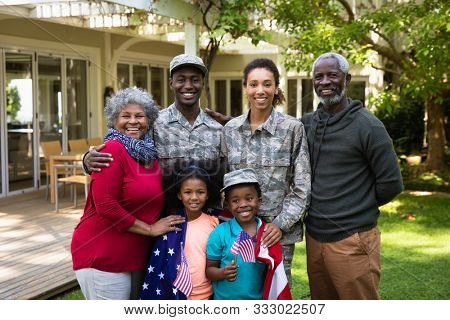 Portrait of a young adult African American male soldier and a young adult mixed race female soldier with thier diverse multi-generation family in the garden outside their home, embracing and smiling