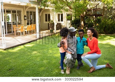 Front view of a young adult African American male soldier in the garden outside his home, kneeling with his arms around his young son and daughter, his mixed race wife beside them, all smiling at each poster