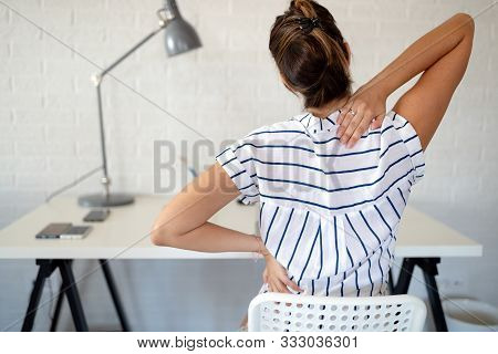 Overworked Woman With Back Pain In Office With Bad Posture