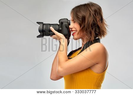 people and photography concept - happy woman photographer in mustard yellow top with digital camera over grey background